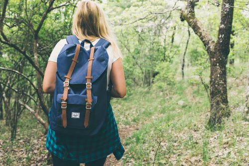 woman with backpack journeying in the woods.